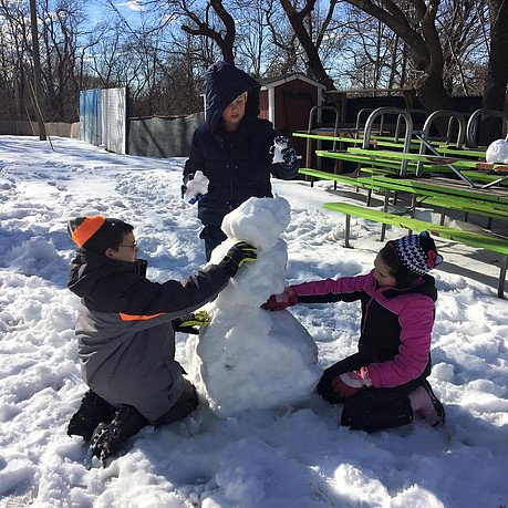 Students at West Hills Academy building a snowman